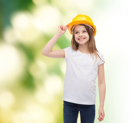 construction and people concept - smiling little girl in protective helmet looking up photo