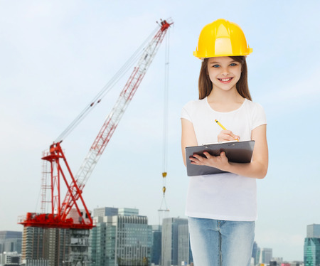 childhood, construction, architecture, building and people concept - smiling little girl in protective helmet with clipboard making notes photo