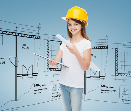 childhood, construction, architecture and people concept - smiling little girl in protective helmet with clipboard and blueprint photo