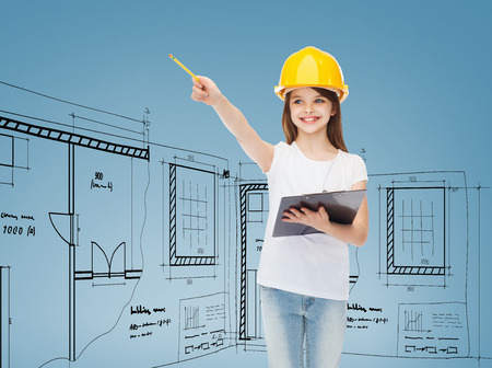 childhood, construction, architecture, building and people concept - smiling little girl in protective helmet with clipboard pointing pencil photo