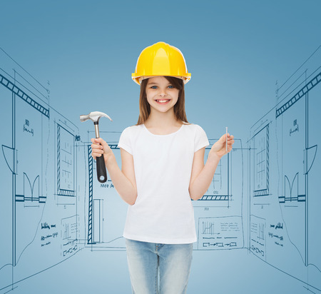 childhood, construction, architecture, building and people concept - smiling little girl in protective helmet with hammer photo