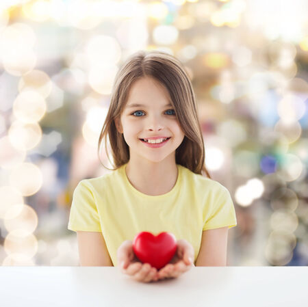 charitable: childhood, love, charity, holidays and people concept - smiling little girl sitting and holding red heart over sparkling background