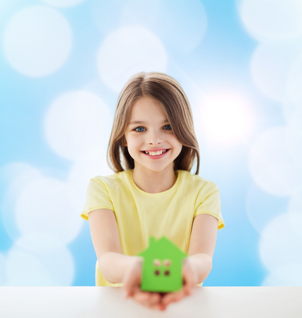 hands holding house: home, education, happiness, childhood and people concept - beautiful little girl sitting at table holding white house cutout over blue background
