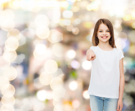 advertising, childhood, gesture, holidays and people - smiling little girl in white t-shirt pointing finger on you over sparkling background photo