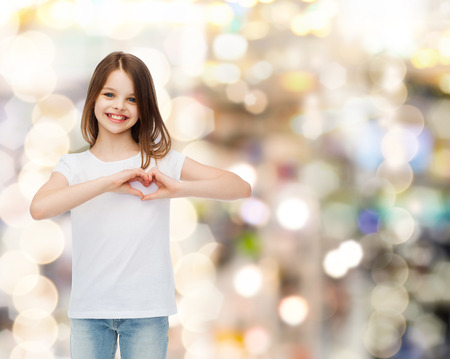 advertising, childhood, charity, holidays and people - smiling girl in white t-shirt making heart-shape gesture over sparkling background