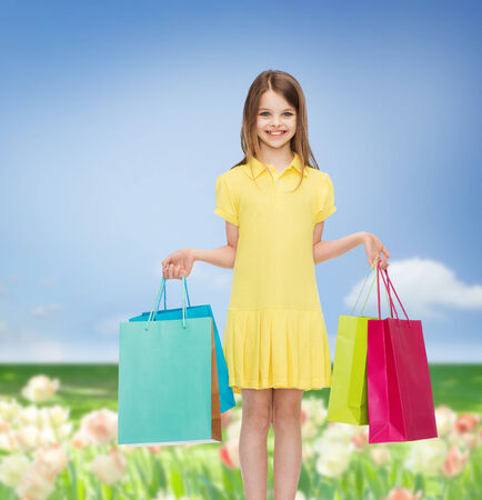 shopping, happiness and people concept - smiling little girl in yellow dress with shopping bags photo