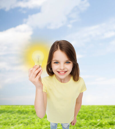 electricity, education and people concept - smiling little girl holding light bulb