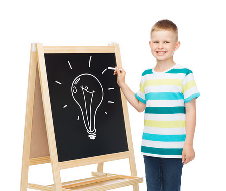 people, childhood and education concept - smiling little boy with bulb drawing on blackboard over white background photo