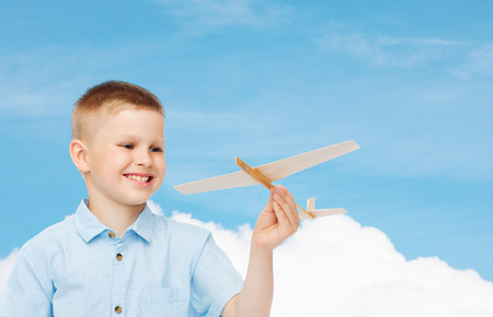 dreams, future, hobby and childhood concept - smiling little boy holding wooden airplane model in his hand over blue sky background photo