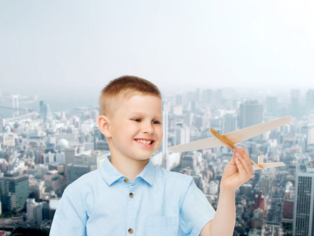 dreams, future, hobby, urban life and childhood concept - smiling little boy holding wooden airplane model in his hand over city background photo