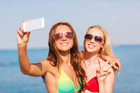 summer vacation, holidays, travel, technology and people concept - two smiling young women on beach making selfie with smartphone over blue sky background photo