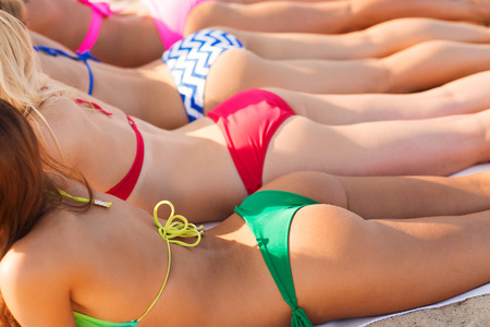 summer vacation, holidays, travel and people concept - close up of young women lying on beach from back photo