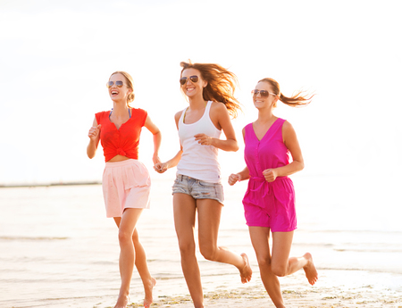 bachelorette party: summer vacation, holidays, travel and people concept - group of smiling young women in sunglasses and casual clothes running on beach Stock Photo