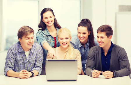 education, technology and internet concept - smiling students looking and pointing at laptop at school photo