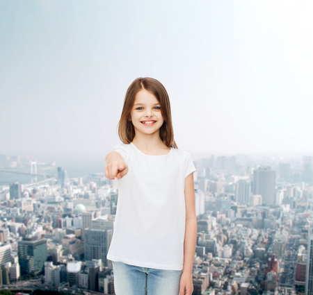 advertising, childhood, gesture and people concept - smiling little girl in white blank t-shirt pointing finger on you over city background photo