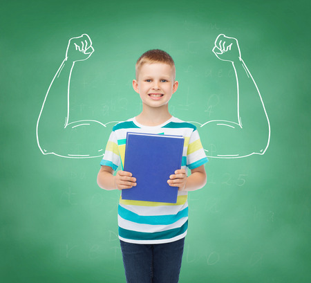education, childhood and school concept - smiling little student boy with book over green board background strong arms drawing photo