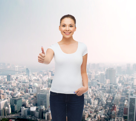 approvement: advertising, gesture and people concept - smiling young woman in blank white t-shirt showing thumbs up over city background