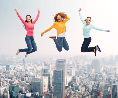 happiness, freedom, friendship, movement and people concept - group of smiling young women and man jumping in air over city background photo