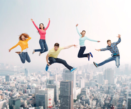 hand movements: happiness, freedom, friendship, movement and people concept - group of smiling teenagers jumping in air over city background Stock Photo