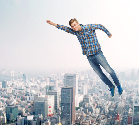 flying man: happiness, freedom, movement and people concept - smiling young man flying in air over city background