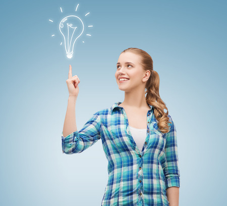 bright idea: happiness, electricity, idea and people concept - smiling young woman pointing finger up to electric bulb over blue background