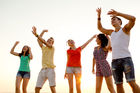 beautiful boys: friendship, summer vacation, holidays, party and people concept - group of smiling friends dancing on beach