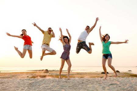 pareja adolescente: amistad, las vacaciones de verano, las vacaciones, el partido y la gente concepto - grupo de amigos sonrientes bailando y saltando en la playa Foto de archivo