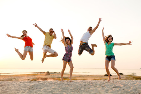 amistad, las vacaciones de verano, las vacaciones, el partido y la gente concepto - grupo de amigos sonrientes bailando y saltando en la playa Foto de archivo