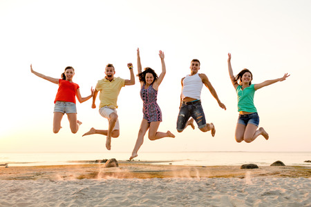 friendship, summer vacation, holidays, party and people concept - group of smiling friends dancing and jumping on beach Фото со стока
