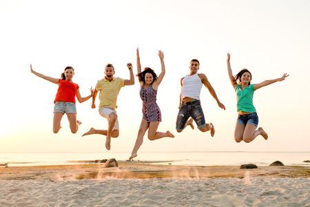 Vriendschap, zomer vakantie, vakantie, feest en mensen concept - groep van lachende vrienden dansen en springen op het strand Stockfoto - 31274905