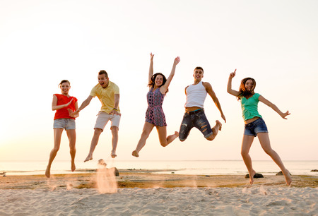 happy people jumping: friendship, summer vacation, holidays, party and people concept - group of smiling friends dancing and jumping on beach Stock Photo