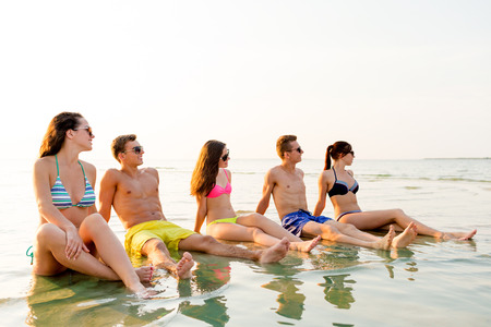 suntanned: friendship, sea, summer vacation, holidays and people concept - group of smiling friends wearing swimwear and sunglasses sitting in water on beach Stock Photo
