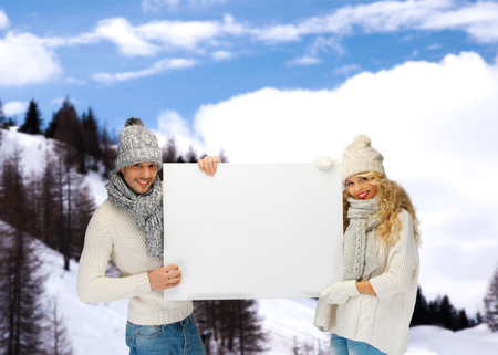 happy couple white background: tourism, winter holidays, christmas, advertising and people concept - smiling couple in winter clothes holding big white blank board over snowy mountains background