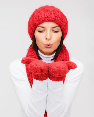 happiness, winter holidays, christmas and people concept - smiling young woman in red hat, scarf and mittens over gray background photo