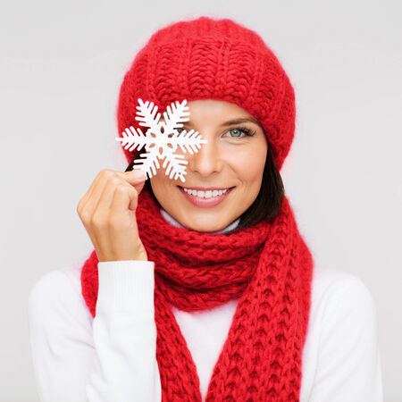 happiness, winter holidays, christmas and people concept - smiling young woman in red hat, scarf and mittens covering one eye with snowflake decoration over gray background photo