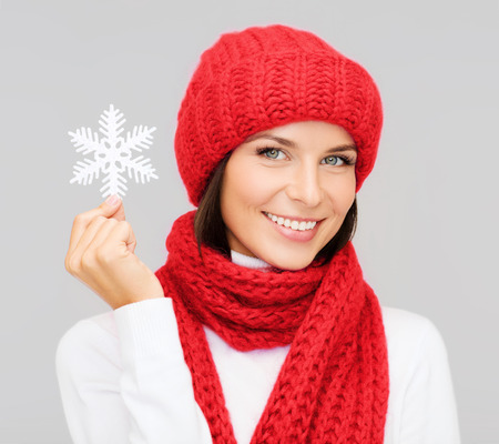 happiness, winter holidays, christmas and people concept - smiling young woman in red hat, scarf and mittens holding snowflake decoration over gray background photo