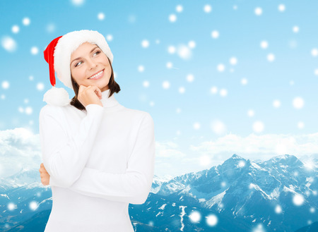 christmas, holidays, winter, happiness and people concept - thinking and smiling woman in santa helper hat over snowy mountains background photo