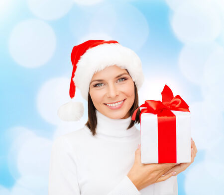 christmas, winter, happiness, holidays and people concept - smiling woman in santa helper hat with gift box over blue lights background photo