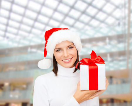 santa helper: christmas, winter, happiness, holidays and people concept - smiling woman in santa helper hat with gift box over shopping center background Stock Photo