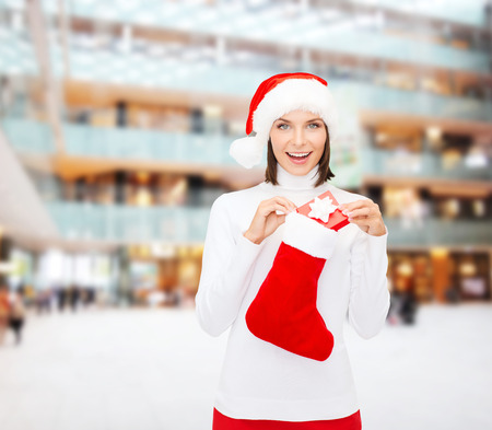 christmas, winter, happiness, holidays and people concept - smiling woman in santa helper hat with small gift box and stocking over shopping center background photo