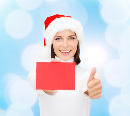 christmas, holdays, people, advertisement and sale concept - happy woman in santa helper hat with blank red card showing thumbs up gesture over blue lights background photo