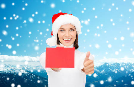 christmas, holdays, people, advertisement and sale concept - happy woman in santa helper hat with blank red card showing thumbs up gesture over snowy mountains background photo