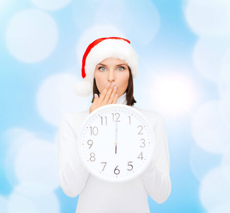 christmas, time, winter and people concept - smiling woman in santa helper hat with clock showing 12 over blue lights background photo