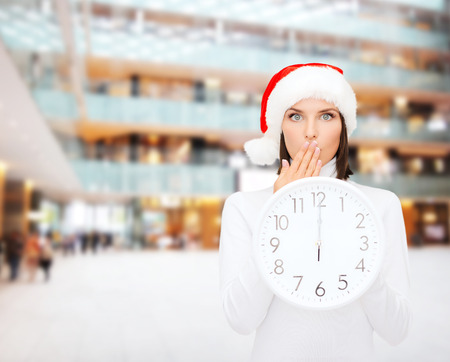 christmas, time, winter and people concept - smiling woman in santa helper hat with clock showing 12 over shopping center background photo