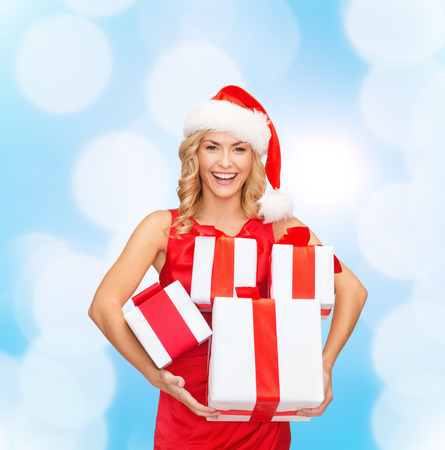fancy box: christmas, winter, happiness, holidays and people concept- smiling woman in santa helper hat with gift box over blue lights background