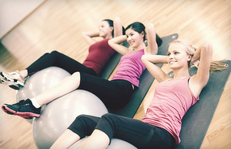 pilates ball: fitness, sport, training, gym and lifestyle concept - group of smiling people working out in pilates class Stock Photo