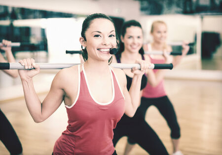 weight gain: fitness, sport, training, gym and lifestyle concept - smiling trainer in front of the group of people working out with barbells in the gym