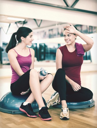 fitness, sport, training, gym and lifestyle concept - two smiling women sitting on the half ball and relaxing after class in the gym photo