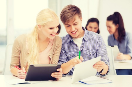 education, technology and internet concept - two smiling students with tablet pc and notebooks at school photo