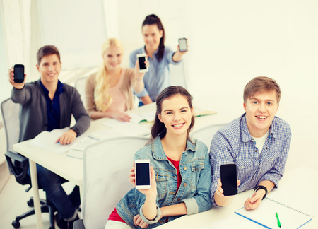 education, school, technology and internet concept - smiling students showing black blank smartphone screens at school photo
